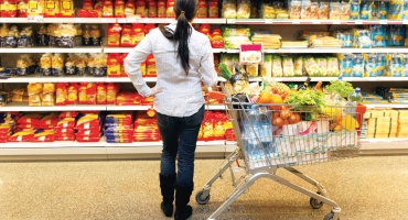 woman looking on products in supermarket aisle