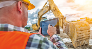 man using tablet at construction