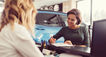 woman signing a car contract
